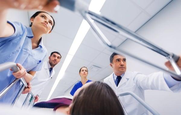medics-with-woman-on-hospital-gurney-at-emergency-706x450